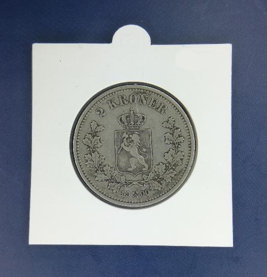 Med en hartberger kan man ta vare på mynter ved å lukke dem i plast. Bildet viser en nær kvadratisk pappskive med en halvsirkelbue i toppen. I midten av skiven er det et stort hull der man kan se en 2 krone fra 1900 dekket av et gjennomsiktig plastlag.
