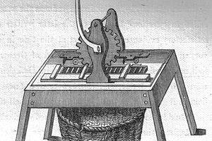 Et bord med et apparat festet til. Apparatet består av en sveive og et tannhjul. Midt på bordet er det et primitivt samlebånd.