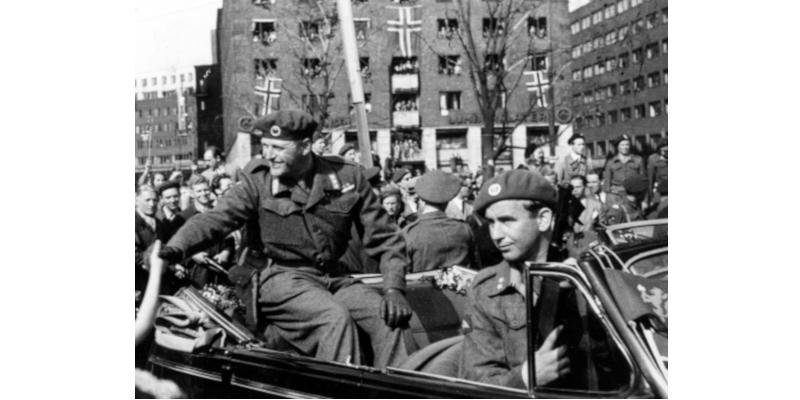 Det var ikke den 8. mai, men den 13. at kronprins Olav kjørte gjennom byen til folkejubel. Men hvem sitter foran med vaktsomt øye?