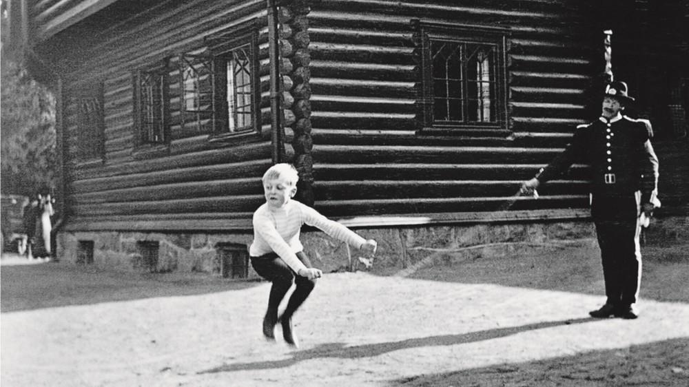 Kong Olav V som ung gutt med en gardist som holder i hoppetau